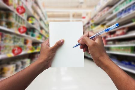 cheque en blanco: mujeres mano compras y la celebración cuaderno vacío para la lista de verificación de su compra en el supermercado