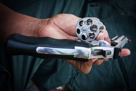 emptied: hand man holding show gun emptied storage cylinder of revolver handgun Stock Photo