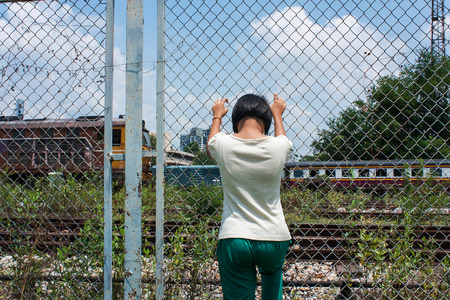 violencia intrafamiliar: muchacha asiática triste asimiento de la mano sola cárcel de ferrocarril, estación de tren