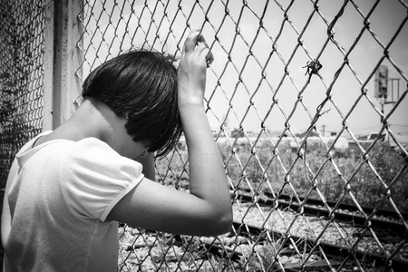 fear child: asian girl sad alone hand hold jail at Railroad,railway station