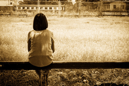 sad asian girl sitting alone  near railway Stations ,vintage tone Stock Photo