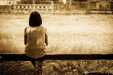 sad asian girl sitting alone  near railway Stations ,vintage tone Stok Fotoğraf