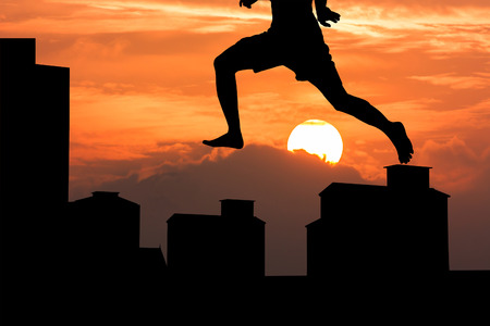dramatic characters: silhouette of young man jumping on the buildingat sunset background
