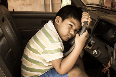 lament: the boy sad alone in the old car,vintage tone Stock Photo