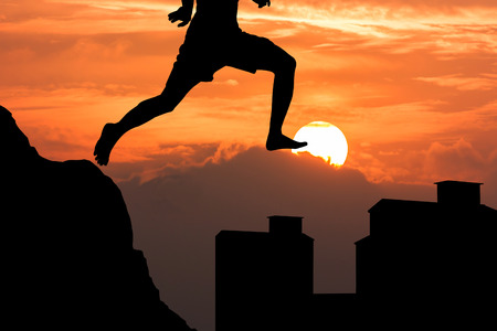 silhouette of young man jumping from the mountain to the buildingon the buildingat on sunset background Stok Fotoğraf