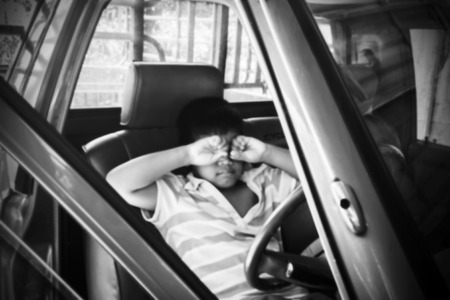 grieve: blurry of the boy sad alone in the old car,black and white Stock Photo