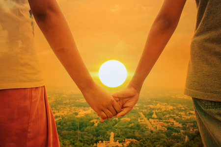 holding hands: happy cute hand child girl couple holding sunset background Stock Photo