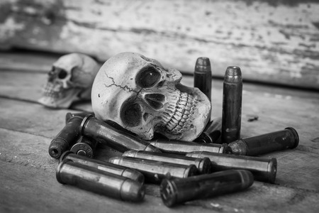 still life of skull human with handcuff and bullet .375 on old wooden background