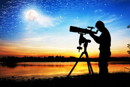 eyepiece: silhouette of young man looking through a telescope at the full moon background
