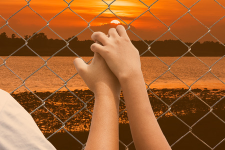 incarcerated: Hand girl in jail at river sunset background Stock Photo