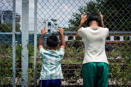 domestic violence: asian girl and boy sad  hand hold jail at Railroad,railway station Stock Photo