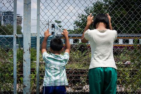 violencia intrafamiliar: muchacha asiática y niño triste asimiento cárcel de ferrocarril, estación de tren Foto de archivo