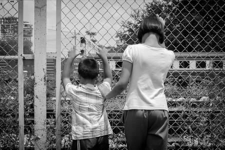 niños abandonados: La muchacha asiática y la cárcel de retención triste mano muchacho en ferrocarril, estación de tren, el negro y el tono blanco