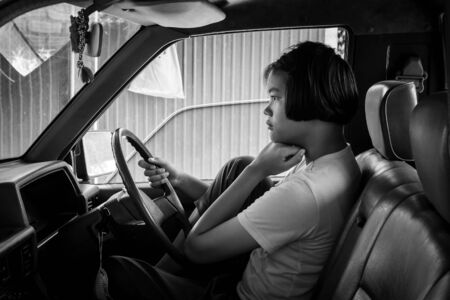 insular: asian girl sad alone sitting in the old car,black and white tone Stock Photo