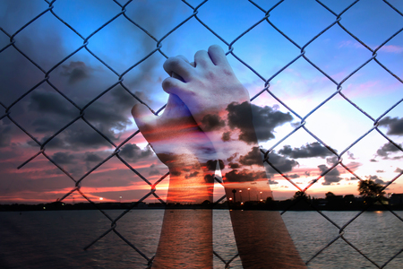 imprison: double exposure of asian girl hand hold jail on sunset at the sea background Stock Photo