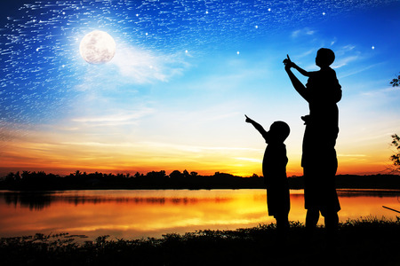 tree silhouettes: Silhouette of father use hand point his son look at full moon on the sky