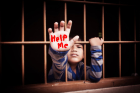 Blurry vintage tone,concept stop bullying ,asian boy hand in jail Foto de archivo