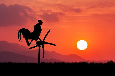 despertar: Los gallos cantan de pie en una turbina de viento. En el fondo de la salida del sol de la mañana