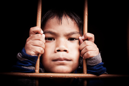 incarcerated: asian boy Hand in jail,vintage tone Stock Photo