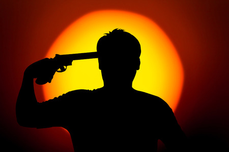 commits: silhouette of Young man commits suicide with his revolver gun