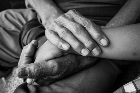 apoyo familiar: niños asiáticos mano toca niño pequeño y mantiene las manos un anciano arrugado, tono blanco y negro