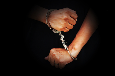 corruption: concept human trafficking,hand girl in shackle on isolate black background Stock Photo