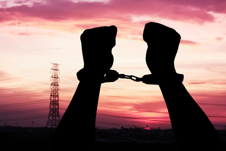 shackle: silhouette of hand men in shackle on sunset in city background