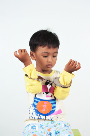 handcuff: little asian boy play handcuff on white background