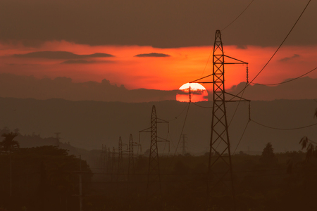 chine: sunset at mountain range and High voltage electricity pylon background Stock Photo