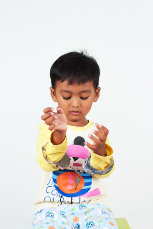 manacle: little asian boy play handcuff on white background