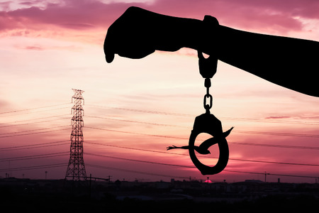 shackle: silhouette of hand women in shackle on sunset in city background