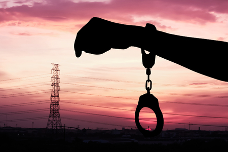 kinky: silhouette of hand women in shackle on sunset in city background