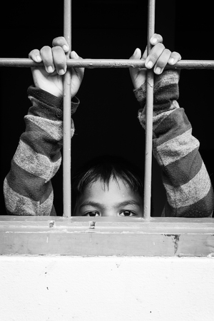 asian boy Hand in jail,black and white tone Stock Photo