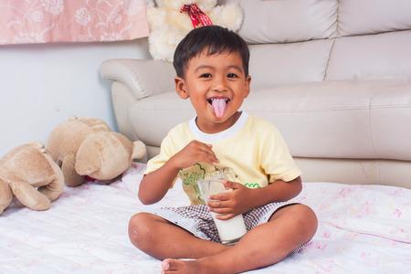 asian boy drinking milk in the room