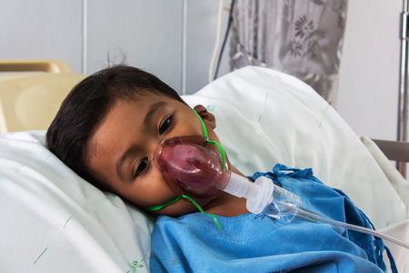 asthma: muchacho enfermo en máscara del inhalador para el niño, el hopital Foto de archivo