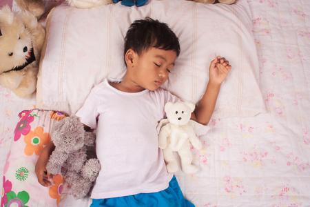 good night: a little asian boy sleep with teddy bear