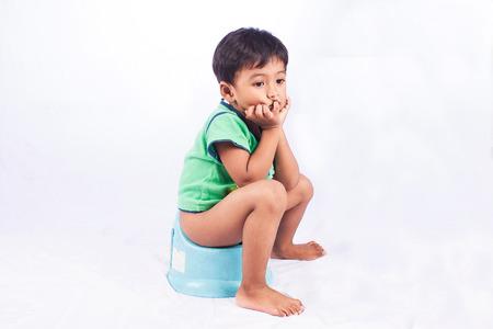 wc: kleinen asiatischen Jungen defecate auf weißem Hintergrund