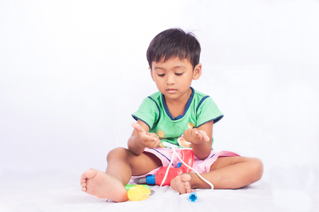 toddler boy: little asian boy play toy tool plastic and count finger on white background