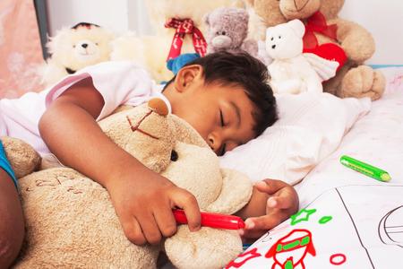 oso de peluche: un peque�o muchacho asi�tico dormir con el oso de peluche y asimiento crayonr, se centran mano