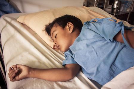 persona enferma: un peque�o muchacho asi�tico enfermo dormir en la cama en el peque�o muchacho asi�tico sue�o enfermo hositala en la cama en el hosital, el tono de la vendimia
