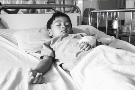 Hand of The Patient on the bed,little boy sick in the Hospital with saline intravenous iv,focus hand,black and white