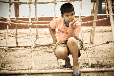 child alone: asian boy sitting alone at playground ,vintage tone Stock Photo