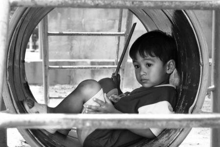 alone boy: asian boy sitting alone at playground ,black and white tone