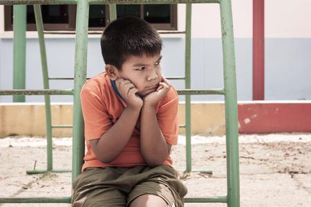 alone: asian boy sitting alone at playground ,vintage tone Stock Photo