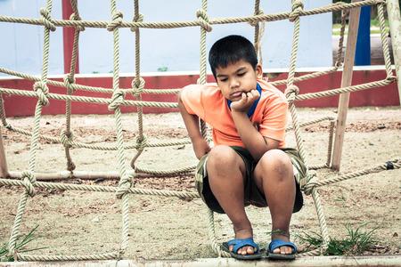joyless: asian boy sitting alone at playground ,vintage tone Stock Photo