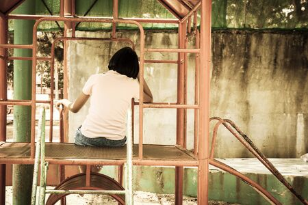 disconsolate: cute asian girl sitting alone at playground