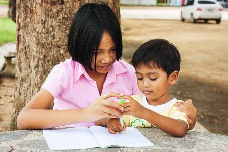 persona escribiendo: linda chica asi�tica y la escritura del muchacho en su libro