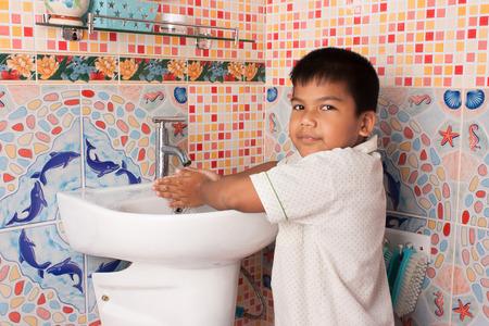 little boy washing hand in the bathroom 版權商用圖片