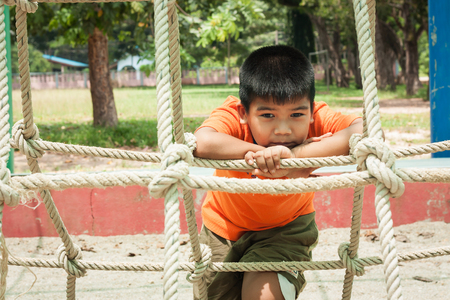 disconsolate: asian boy sitting alone at playground
