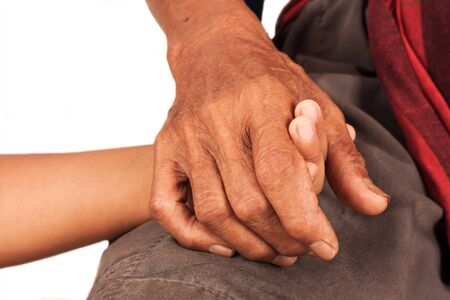 endearment: asian kids little boy hand touches and holds an old man wrinkled hands Stock Photo